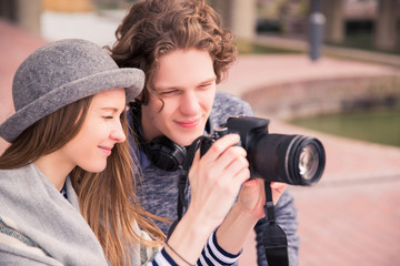 Wonderful couple sits and looks at photo camera, outdoors