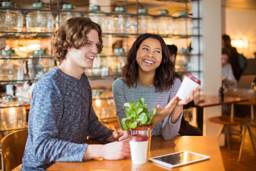 Smiling couple sits in cafe with cups of coffee and the tablet, in time of a break, inside