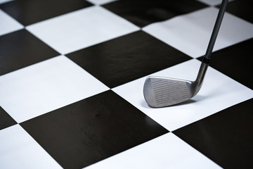 Close up shot of golf club on checkered background.