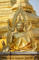 Front of sitting Thai Buddha statue that wear golden clothes.