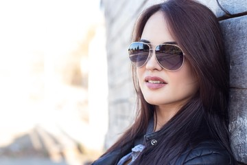 Young beautiful woman in sunglasses. Portrait of a young woman on a wooden background. Beautiful brunette in black jacket.