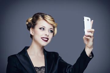 Portrait d'une jeune femme en tailleur, se prenant en photo avec son téléphone portable
