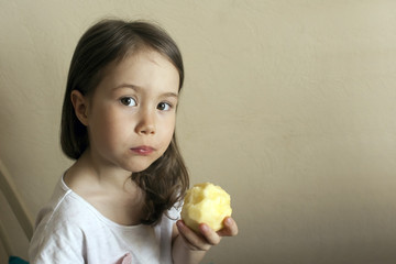 The child eats a peeled apple. The baby's teeth fell out