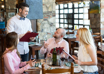 Adults having dinner and waiter