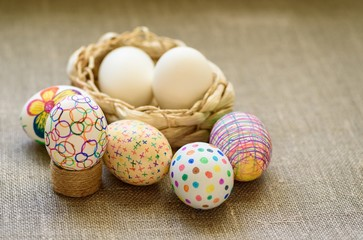 Easter eggs in a wicker basket on the tablecloth of burlap