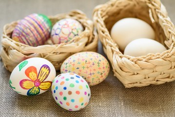 Easter eggs in a 2 wicker baskets on the tablecloth of burlap