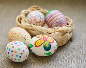 Easter eggs in a 1 wicker basket on the tablecloth of burlap