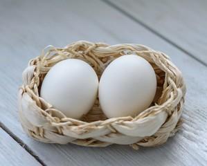 2 eggs in a wicker basket on a wooden table