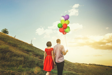 happy couple of man and woman in love, with multicolored balloons