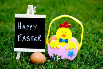 Easter egg hunt egg felt basket with Chick decoration on grass background with blackboard