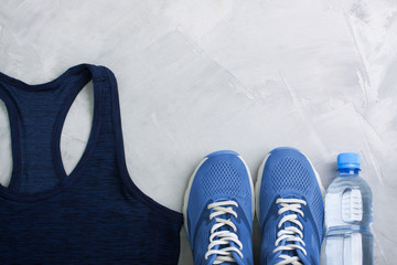 Flatlay sport composition with outfit blue sneakers and t-shirt