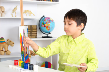 the boy draws on an easel paints