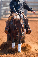A front view of western rider sliding the horse in the dirt