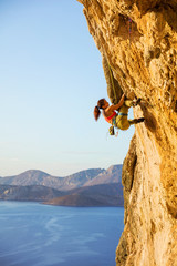 Young woman climbing challenging route