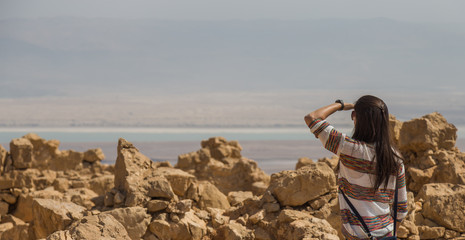 Girl looking the Dead Sea from the ruins of the ancient Masada fortress in the Judaean Desert, Israel