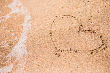 Drawing of a heart on a yellow sand at a beautiful seascape background.