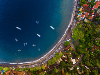 Aerial shot of a calm lagoon with boats and buildings. Bali, Indonesia