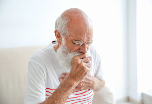 Coughing senior man sitting on sofa