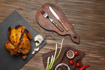Slate plate with roasted beer can chicken on wooden background