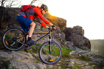 Cyclist Riding Mountain Bike Down Rocky Hill on the Spring Trail at Sunset. Extreme Sports Concept.