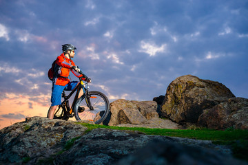 Cyclist Resting on Mountain Bike on the Spring Rocky Trail at Beautiful Sunset. Extreme Sports and Adventure Concept.