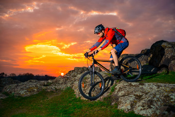 Cyclist Riding Mountain Bike Down Spring Rocky Hill at Beautiful Sunset. Extreme Sports and Adventure Concept.