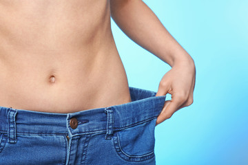 Diet concept. Young beautiful woman in big jeans on light background