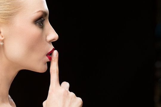 Attractive mature woman making shushing gesture