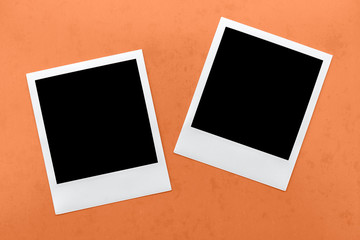 two blank instant camera film frames on orange background.