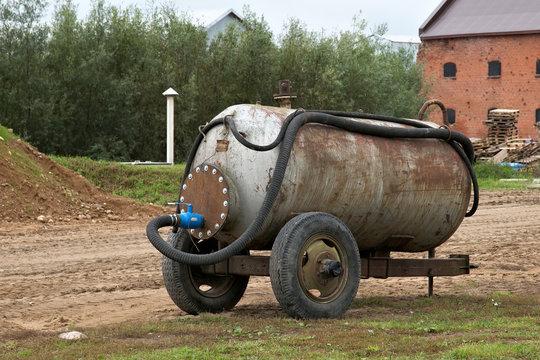 Old rusty water tank on wheels.