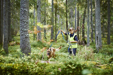 Sweden, Uppland, Rison, Volunteer with dog helping emergency services find missing people