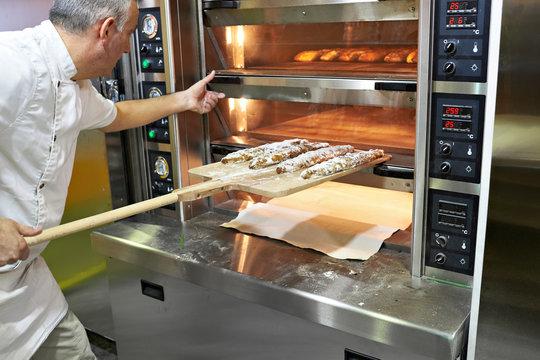 Baker bakes bread in oven