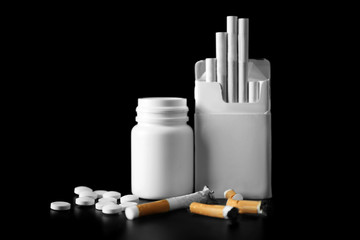 Damaged cigarettes, pack and drugs on black background