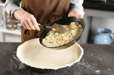 Woman making delicious chicken pot pie on kitchen table
