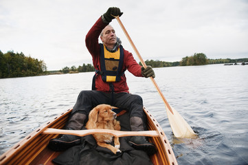 Sweden, Smaland, Mature man and dog in boat on lake