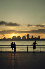 USA, New York, New York City, People looking at Manhattan skyline at sunset