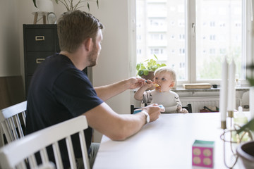 Sweden, Father helping son (12-17 months) eating at table