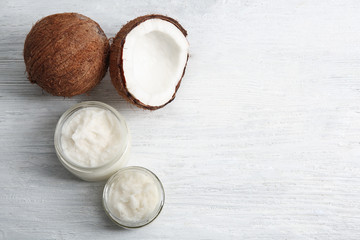 Jars with fresh coconut oil and nut on wooden background