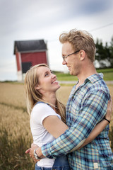 Finland, Uusimaa, Siuntio, Mid adult couple embracing in wheat field
