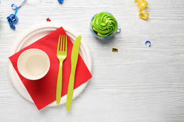 Plate with birthday cupcake and cup on wooden table