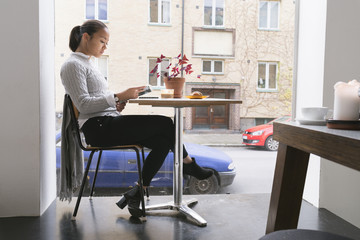 Sweden, Woman sitting in cafe with building in background