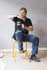 Sweden, Man sitting on chair and holding thermos