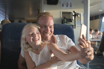 Sweden, Girl (6-7) and father taking selfies with cell phone in ship cabin