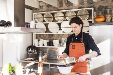 Sweden, Vastmanland, Man cooking dish