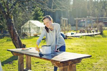 Finland, Paijat-Hame, Heinola, Mid adult woman oiling wooden table in garden