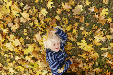 Sweden, Sodermanland, Stockholm, Sodermalm, Langholmen, Blonde boy (2-3) lying down in autumn foliage