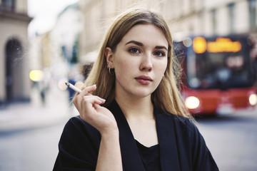 Sweden, Uppland, Stockholm, Kungsholmen, Portrait of young woman smoking in street