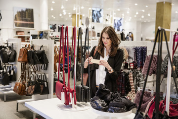 Sweden, Woman photographing purses in shop