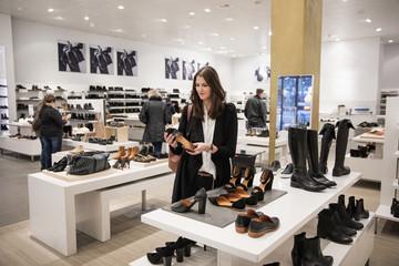 Sweden, Woman choosing shoes in shop