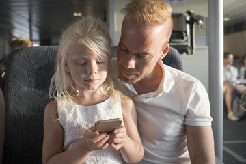 Sweden, Girl (6-7) and father using cell phone in ship cabin